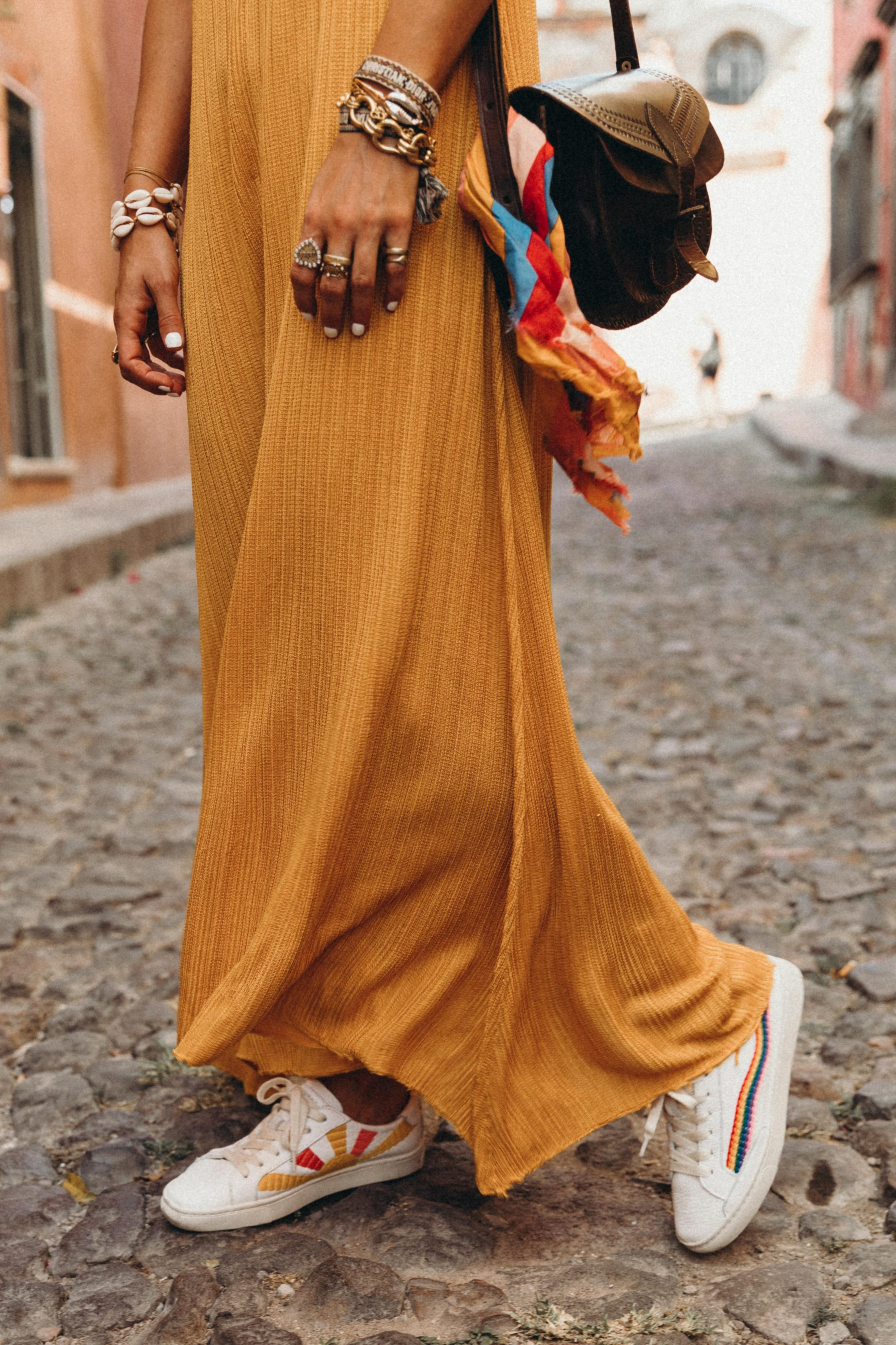Sara of Collage Vintage wearing a long mustard dress and embroidered sneakers